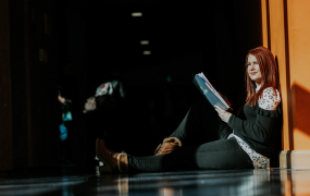 Woman sits on a floor holding a book and looking into the distance