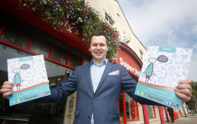 Image of AsIAm CEO Adam Harris holding the new resource outside a Supervalu shop