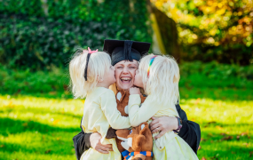 Woman in graduation robes hugs her two daughters