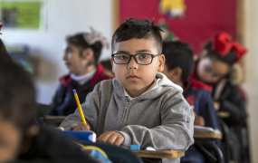 A child sitting in a classroom holding a pencil
