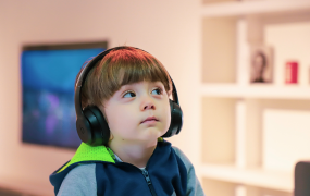 An autistic child sits looking upwards while wearing noise cancelling headphones