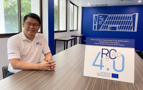Project leader Dr Pisut Koomsap pictured in a board room in the Asian Institute of Technology. Dr Koomsap is pictured sitting with his hands on a table. Also on the table is a sign saying ReCap 4.0