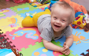 Stock image of a male child with mixed abilities plays on a colourful soft play mat
