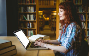 Side profile of a woman with red hair wearing a check shirt sits in a library typing on a laptop