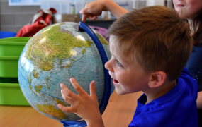 A male child wearing a blue t-shirt sitting in a classroom pointing at a globe