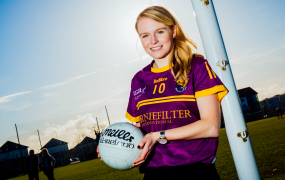 Female student holding a football and standing by a goalpost wearing a GAA jersey