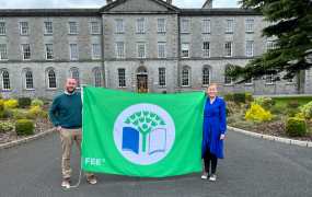 A man & woman pictured holding the Green Campus Flag on the grounds of MIC Thurles with the MIC Thurles building in the background