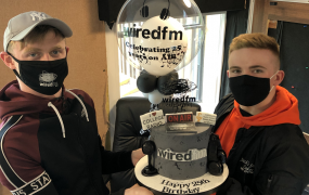 Two male students wearing masks holding a birthday cake and a balloon