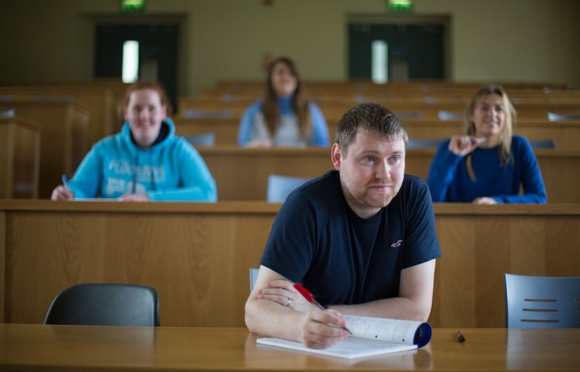 male mature student in a lecture theatre in MIC Thurles with several students behind him