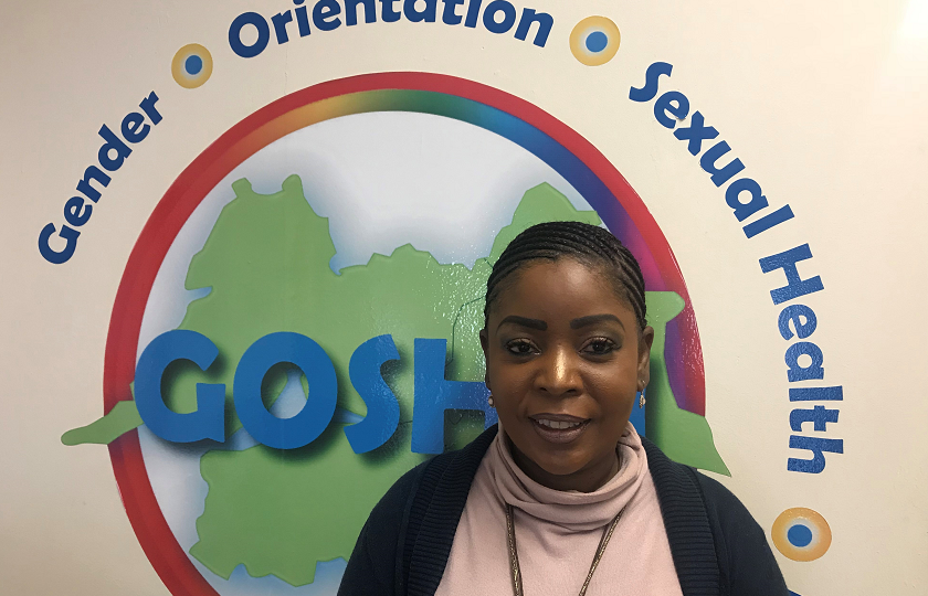 Ann Piercy from GOSHH (Gender, Orientation, Sexual Health, HIV) pictured in front of the GOSHH logo
