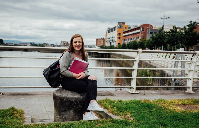 Female student sitting with the River Shannon in the background