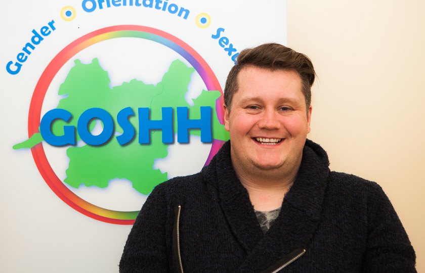 Patrick McElligott from GOSHH (Gender, Orientation, Sexual Health, HIV) standing in front of the GOSHH logo