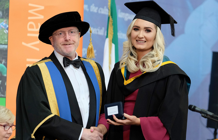 Louise Curtin pictured in her graduation gowns being presented with a medal from Professor Eugene Wall, President of MIC