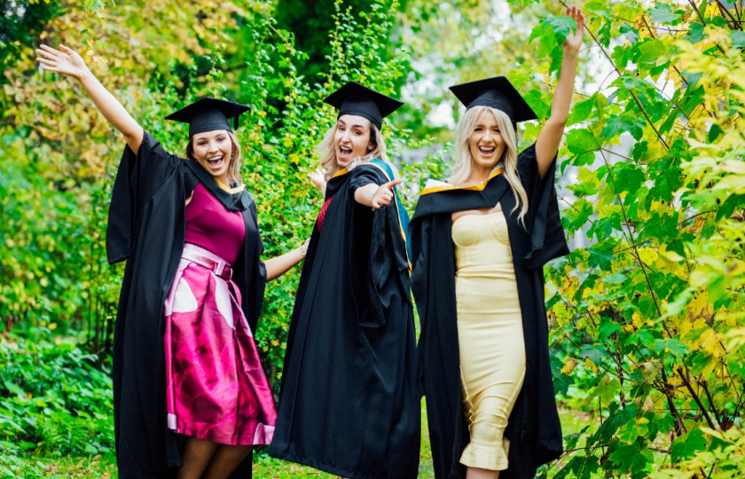 Three female MIC students with graduation robes